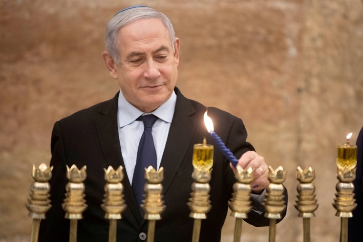 Israeli Prime Minister Benjamin Netanyahu, lights a Hanukkah candle at the Western Wall, the holiest site where Jews can pray in Jerusalem's old city, December 22, 2019. Reuters