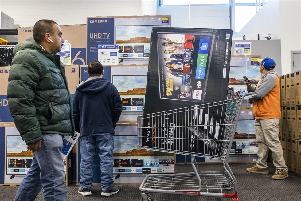 Shoppers carry televisions purchased from a store during Black Friday sales in Los Angeles, Friday. Black Friday is a sales offer on the Friday following Thanksgiving Day which has become a major shopping day in the United States. /AFP-Yonhap