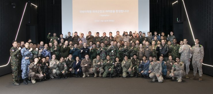 Foreign military officers pose during a visit to the headquarters of Hanwha Group in Seoul, Dec. 12. Courtesy of Hanwha Group
