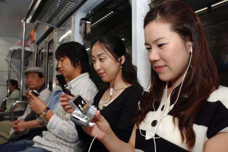 Subway passengers watch mobile TV broadcasts via their cellphones in this 2008 file photo. The mobile TV service, is on the brink of closure on a decline in viewership. / Korea Times file