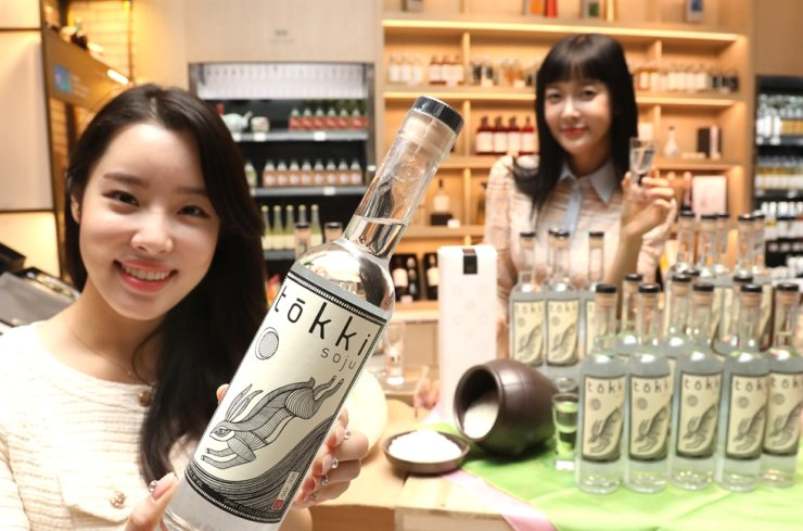 Models pose with Tokki Soju, the first American handcrafted traditional rice soju, at a Shinsegae Department Store branch in Seoul, Dec. 18. / Courtesy of Shinsegae Department Store