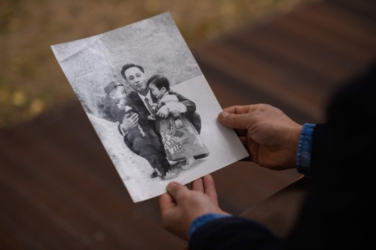 In a photo taken on Nov. 10, Hwang In-cheol shows a photo of his father, in Seoul. AFP