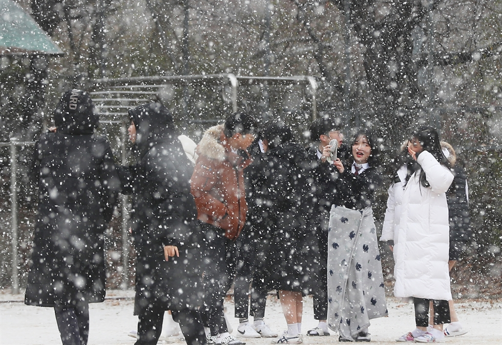 Snow falls around the feet of a bronze girl statue symbolizing Korean women forced into sexual slavery for Japanese troops during World War II, at Limjingak Pavilion in Paju, Gyeonggi Province, Tuesday. Seoul, Gyeonggi and western parts of the country had snow on Tuesday as temperatures fell below zero. The freezing weather will continue throughout the week. Yonhap