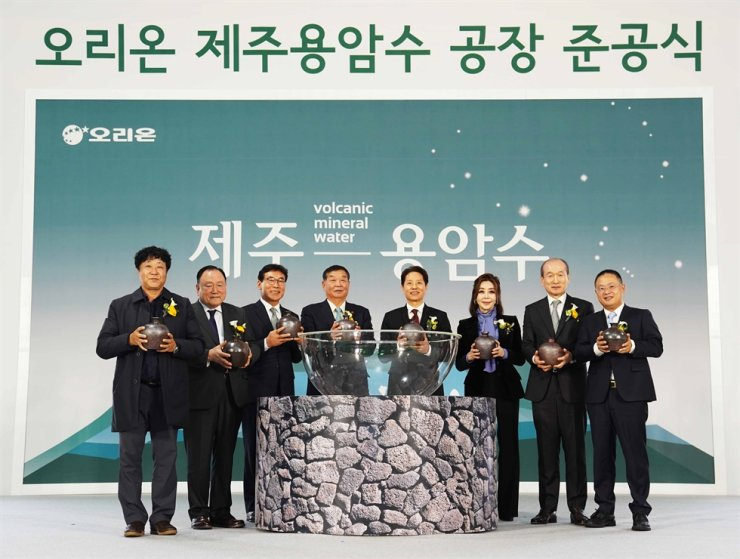 Orion Chairman Dam Chul-gon, fifth from left, with participants celebrating the completion of the company's mineral water plant on Jeju Island, Tuesday. Second from right is Vice Chairman Huh In-cheol. Courtesy of Orion