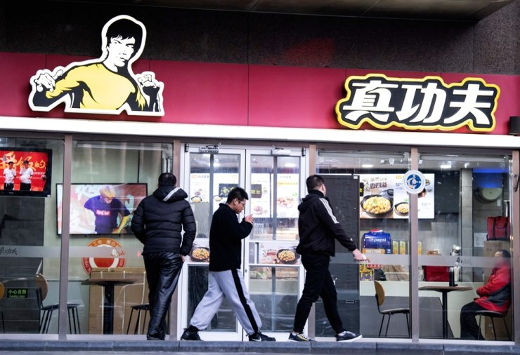 People walk past the restaurant Real Kung Fu, or Zhen Gongfu in Mandarin, run by fast food chain Kungfu Catering Management, in Beijing on December 26, 2019. AFP