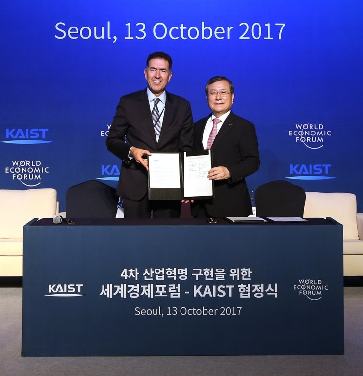 KAIST President Shin Sung-chul, right, poses with Murat Sonmez, a managing director who heads the World Economic Forum's Center for the Fourth Industrial Revolution, after signing an MOU in Seoul in October 2017. / Courtesy of KAIST