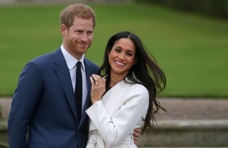 In this file photo taken on on November 27, 2017, Britain's Prince Harry stands with his fiancee US actress Meghan Markle as she shows off her engagement ring whilst they pose for a photograph in the Sunken Garden at Kensington Palace in west London, following the announcement of their engagement. AFP