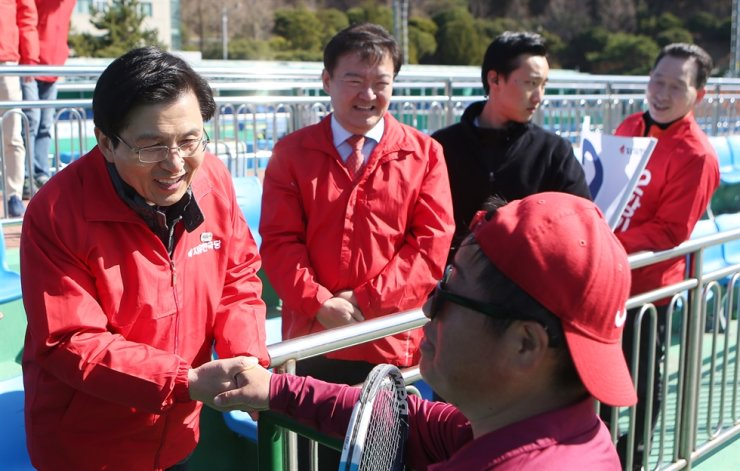 Liberty Korea Party Chairman Hwang Kyo-ahn shakes hands with a resident in Changwon, South Gyeongsang Province, while supporting a candidate from the party for a by-election in this March 24, 2019 photo. Although a handshake is the traditional way for politicians to express friendliness to voters, candidates for the April 15 general election are now avoiding it due to public concerns over the spread of the virus. / Yonhap