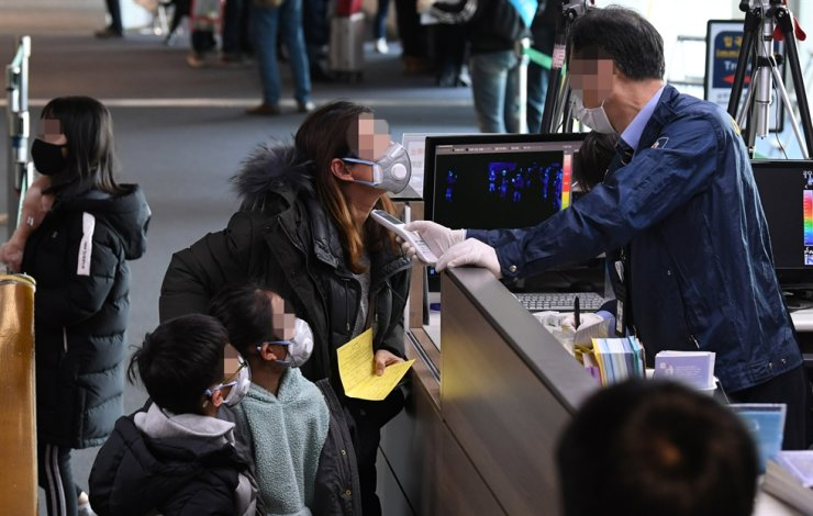 A quarantine official checks passengers arriving at Incheon International Airport from China for signs of fever and other symptoms amid growing concerns over the spread of the Wuhan coronavirus, Tuesday. / Yonhap