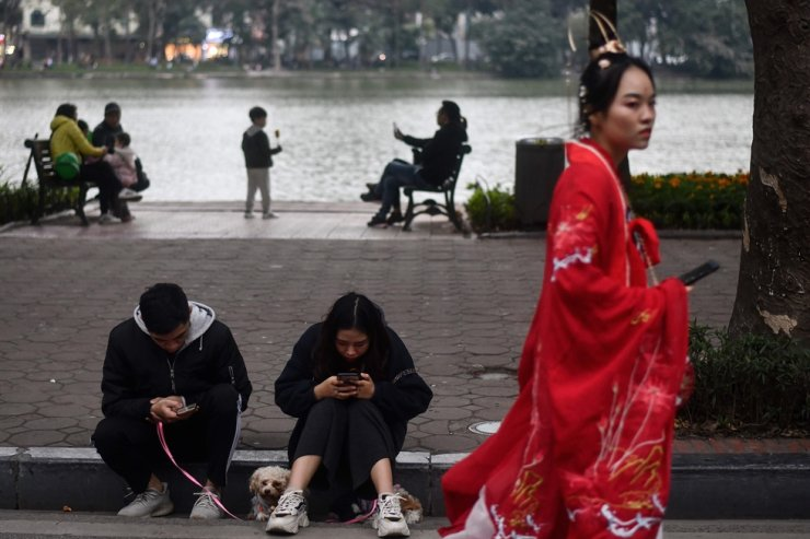 A Vietnamese couple use their smartphones while sitting with their dogs by the Hoan Kiem lake in Hanoi on Jan. 12, 2020. AFP-Yonhap