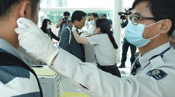 Quarantine officers check the temperatures of passengers arriving at Incheon International Airport, on flights from Dubai, in this Sep. 10, 2018 file photo. The Korea Centers for Disease Control and Prevention are taking preventive measures against the spread of a mysterious pneumonia from China, although no suspected cases were reported in Korea yet. Korea Times file