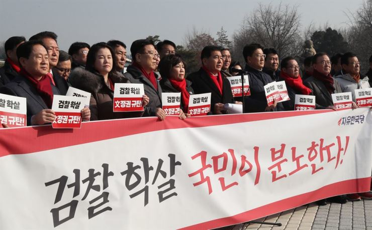Lawmakers of the ruling Liberty Korea Party (LKP) hold a rally in front of Cheong Wa Dae, Friday, against Justice Minister Choo Mi-ae's recent reassignment of senior prosecutors. They are holding a sign that reads 'the people are angry with the massacre of the prosecution.' Yonhap