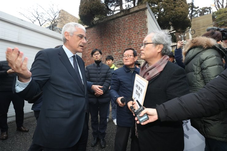 Deputy Chief of Mission Agustin Anguera de Sojo Baeza, left, at the Spanish Embassy in Seoul speaks with a bereaved family member of a Korean student killed in Madrid, during a protest outside the embassy, Dec. 30. Lee Ji-hyeon, 32, was hit in the head by a stone fragment from a government building, Dec. 20. The Spanish authorities claim bad weather caused the accident, but protesters claim the death was through poor management of the building and that Spanish and Madrid authorities were responsible. The protest came as the two countries mark the 70th anniversary of diplomatic relations in 2020. / Yonhap