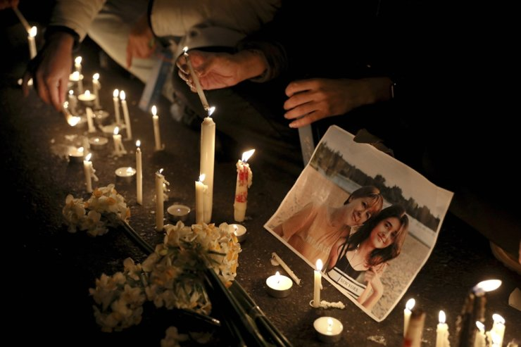 Candles sit in front of a picture of a victim at a candlelight vigil to remember those killed in the Ukraine plane crash, at the gate of Amri Kabir University that some of the victims of the crash were former students of, in Tehran, Iran, Saturday, Jan. 11, 2020. Iran on Saturday, Jan. 11, acknowledged that its armed forces 'unintentionally' shot down the Ukrainian jetliner that crashed earlier this week, killing all 176 aboard, after the government had repeatedly denied Western accusations that it was responsible. /AP
