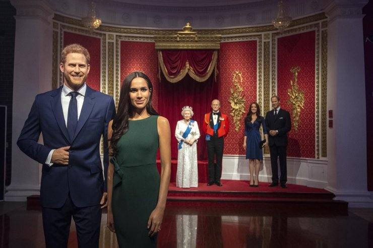 The figures of Britain's Prince Harry and Meghan, Duchess of Sussex, left, are moved from their original positions next to Queen Elizabeth II, Prince Philip and Prince William and Kate, Duchess of Cambridge, at Madame Tussauds in London, Thursday Jan. 9, 2020. Madame Tussauds moved its figures of Prince Harry and Meghan, Duchess of Sussex from its Royal Family set to elsewhere in the attraction. AP