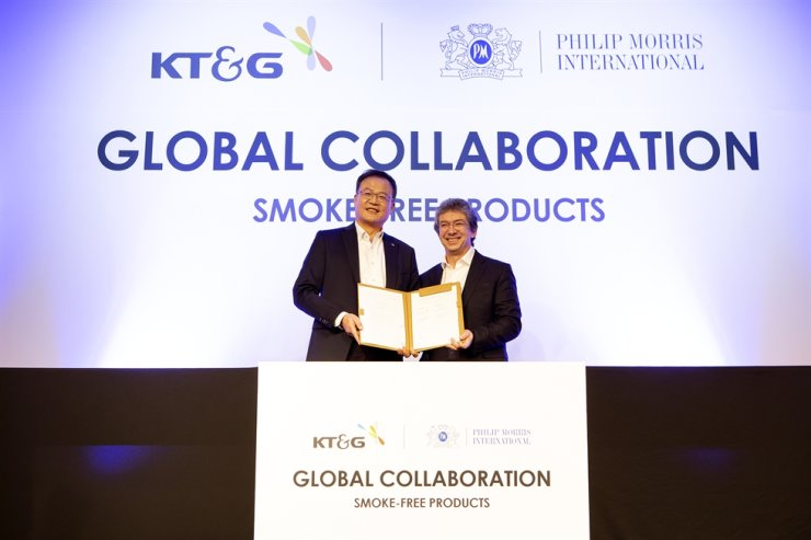 KT&G CEO Baek Bok-in, left, and Philip Morris International CEO Andre Calantzopoulos pose after signing a partnership agreement at the Four Seasons Hotel in Seoul, Wednesday. Courtesy of KT&G