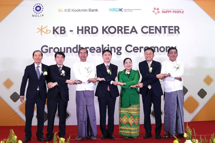 Choi Chang-su, second from right, managing director at KB Kookmin Bank's global business, poses with Myanmar's Human Resources Minister Daw Moe Moe Su Kyi, third from right, and participants to the groundbreaking ceremony of the Korean language test facility in Yangon, Myanmar, Jan. 10. KB will establish the four-story building to raise awareness of the Korean language in the country. Courtesy of KB Kookmin Bank