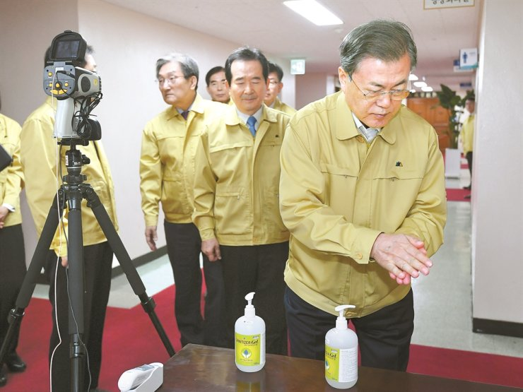 President Moon Jae-in cleans his hands with hand sanitizer ahead of a meeting at the Government Complex in Seoul, Thursday, to discuss the government's response to the coronavirus outbreak. Moon said his administration will take every necessary measure to contain the deadly virus and called for a strict response to fake news linked to the disease. / Yonhap