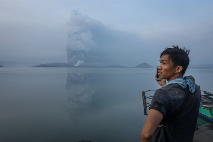 A man records on his mobile phone the Taal volcano's eruption in Talisay, Batangas, Philippines, 13 Jan. 2020. Thousands of people have been ordered to evacuate as authorities in the Philippines raised the alert due to the increased activity of the Taal volcano, located in an island near Manila. The Philippine Institute of Volcanology and Seismology raised the alert level from 1 to 3 and then 4 - on a scale of 5, after an increase in the activity of the crater resulted in an eruption spewing steam and ash up to one-kilometer high. EPA
