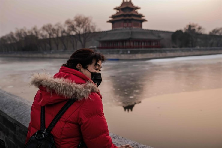 A woman wearing protective facemask to help stop the spread of a deadly SARS-like virus, which originated in the central city of Wuhan, looks out on the outskirts of the Forbidden City (back) in Beijing on Jan. 25, 2020. AFP