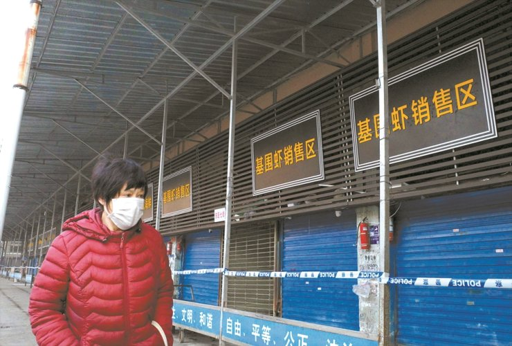 In this file photo taken on Jan. 12, 2020, a woman walks in front of the closed Huanan wholesale seafood market, where health authorities say a man who died from a respiratory illness had purchased goods from, in the city of Wuhan, Hubei province, China. A second person has died in China from a mystery virus that has stricken dozens and appeared in two other Asian countries, officials said. AFP