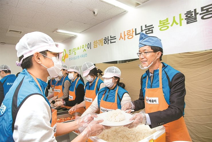 Export-Import Bank of Korea (Eximbank) CEO Bang Moon-kyu, right, hands out food with bank employees at a volunteer service center nearby Seoul Station, Tuesday. The state-run lender's chief and employees volunteered at the facility on the occasion of the Lunar New Year (Seollal) holiday that begins Friday. / Courtesy of Eximbank