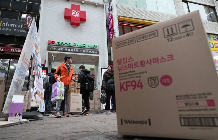 A tourist leaves a pharmacy in the Myeong-dong shopping district after buying a box of masks amid mounting fears over the spread of the deadly coronavirus, Monday. / Yonhap