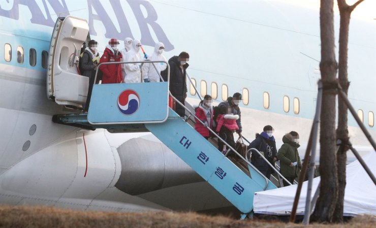 Koreans from Wuhan, China, arrive at Gimpo International Airport, Friday. A total of 350 of the first batch of 368 people will stay at two government-run facilities in Jincheon, North Chungcheong Province, and in Asan, South Chungcheong Province, for the 14 days. / Yonhap