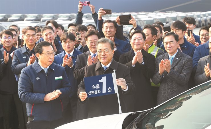 President Moon Jae-in, center, congratulates the first export of a Niro-branded eco-friendly vehicle developed by Kia Motors during his visit to the Pyeongtaek-Dangjin seaport, a trade hub of South Korea's vehicle exports located 70 kilometers southwest of Seoul, Friday. Yonhap
