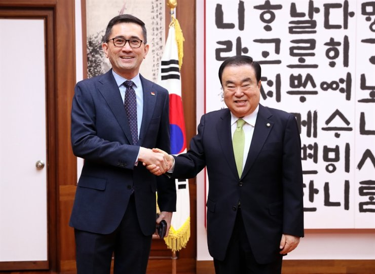 Singaporean Ambassador to Korea Eric Teo Boon Hee, left, and National Assembly Speaker Moon Hee-sang shake hands during the envoy's visit to the Assembly, Jan. 7. Moon addressed Singapore as a 'core partner' for Korea's New Southern Policy aimed at elevating ties with the 10-member ASEAN, and expressed hope the two countries will continue to cooperate and co-prosper in various fields. / Yonhap