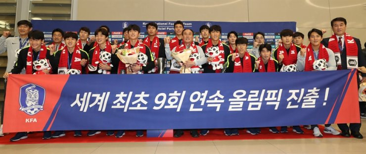South Korean men's Olympic football team and head coach Kim Hak-bum, center, pose for a photo at Incheon International Airport, just west of Seoul, Tuesday, after returning from winning the Asian Football Confederation (AFC) U-23 Championship in Thailand. Yonhap