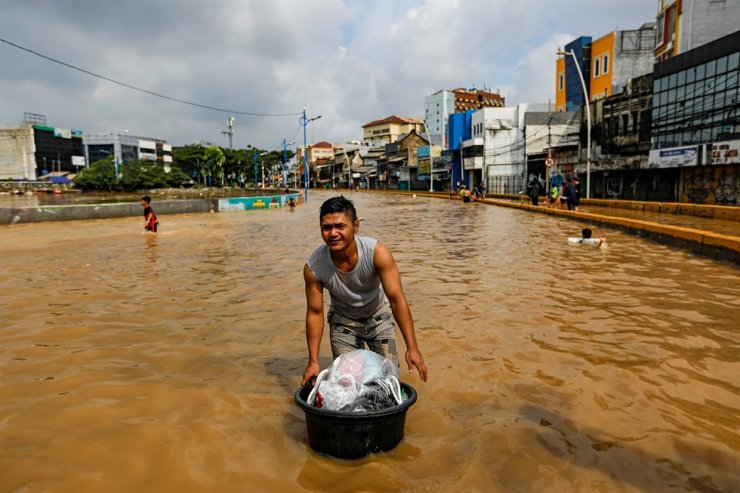 Man carries his belongings across floodwaters at the Jatinegara area after heavy rains in Jakarta, Indonesia, January 2, 2020. Reuters