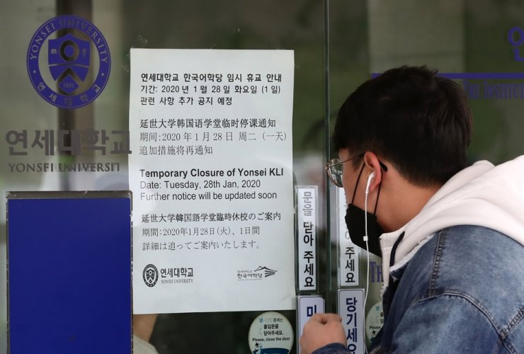 A student looks at a notice of temporary closure of a lecture building at Yonsei University's campus in Seoul, Tuesday. Yonhap