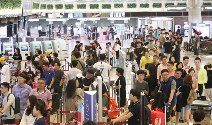 Passenger wait in long line at Gimpo International Airport in this photo taken in July last year. / Yonhap