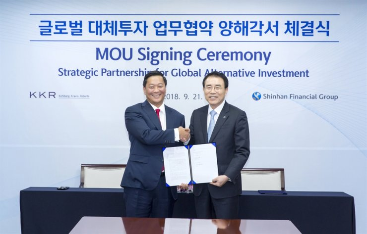 Shinhan Financial Group Chairman Cho Yong-byoung, right, shakes hands with KKR Co-President Joseph Bae at the Shinhan Financial Group headquarters in Seoul, after signing a memorandum of understanding regarding a strategic partnership for global alternative investment on Sept. 21, 2018 file photo. / Courtesy of Shinhan Financial Group