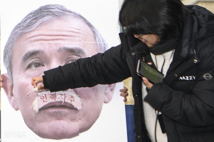 A protester damages a photo of U.S. Ambassador to South Korea Harri Harris during a rally near the U.S. Embassy in Seoul on Dec. 13, 2019. Korea Times file