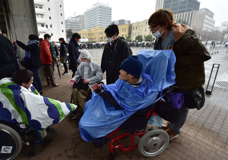 People in wheelchairs attend a lottery for admission tickets to the court hearing of Satoshi Uematsu, accused in the 2016 murder of 19 disabled people at a Japanese care home, outside the Yokohama District Court in Yokohama, Kanagawa prefecture on January 8, 2020. AFP