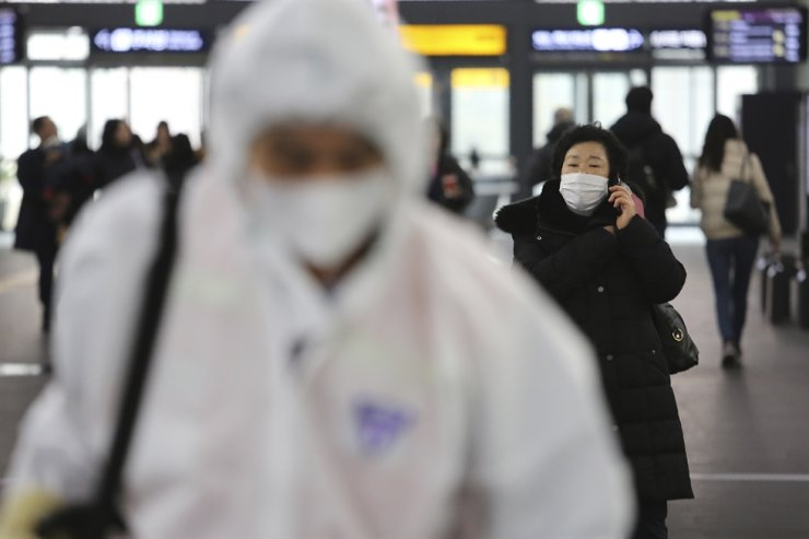 A woman wears a mask as an employee works to prevent a new coronavirus at Suseo Station in Seoul, Friday, Jan. 24, 2020. AP