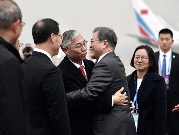 President Moon Jae-in hugs Chinese Ambassador Qiu Guohong at an aiport in Chengdu, China, in December 2019 before taking off to Seoul. Courtesy of Cheong Wa Dae
