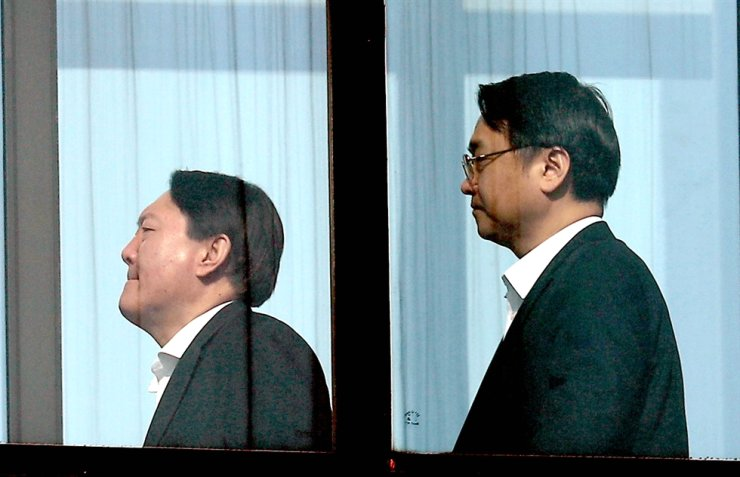 Prosecutor General Yoon Seok-yeol, left, and his colleague are on their way to have lunch in the Supreme Prosecutor's Office in southern Seoul, Friday./ Yonhap