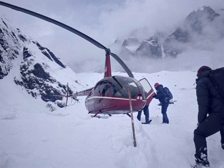 In this Saturday, Jan. 18, 2020 photo, trekkers are being rescued in a helicopter a day after an avalanche hit Mount Annapurna trail in Nepal. Special army and government rescue personnel were searching again on Monday for four Korean trekkers and their three Nepali guides lost since an avalanche swept a popular trekking route in Nepal's mountains. AP