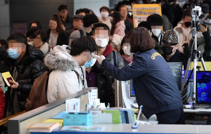 A quarantine officer at Incheon International Airport checks the temperature of passengers arriving from China, Tuesday, amid the spread of coronavirus. / Yonhap