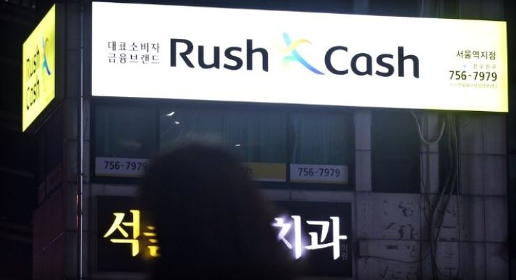 A passenger walks past an electric sign of the nation's largest private moneylending brand, Rush & Cash, operated by Apro Financial, in central Seoul in this file photo. Yonhap