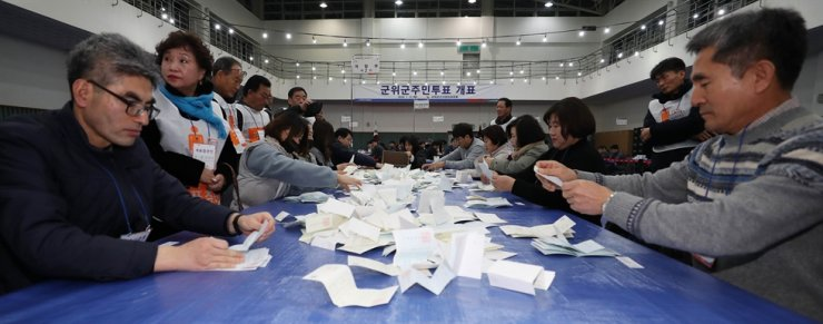 Officials count ballots at Gunwi County, North Gyeongsang Province, Tuesday, after a referendum to select a final candidate to host the new Daegu airport. / Yonhap