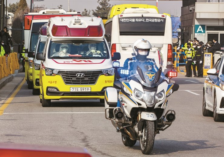 Ambulances carry away Korean evacuees from Wuhan, who showed symptoms associated with the coronavirus infection, upon their arrival at Gimpo International Airport, Friday. Among 368 Korean evacuees from the coronavirus-hit Chinese city, 18 were sent to hospitals, while the remaining 350 were quarantined in government-run facilities. / Korea Times photo by Shim Hyun-chul