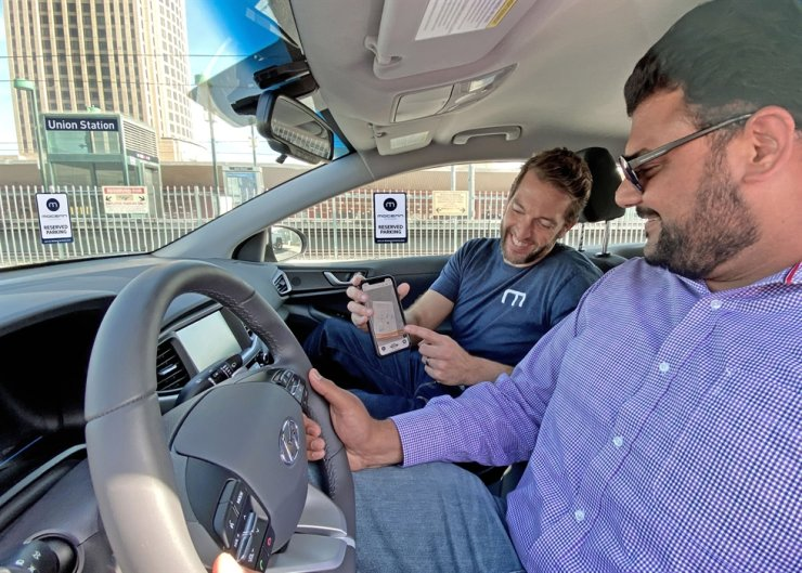 Mocean Lab Vice President Dave Gallon, left, demonstrates Mocean Carshare car-sharing service to a customer at Union Station, Los Angeles, Jan. 4 (local time). Courtesy of Hyundai Motor