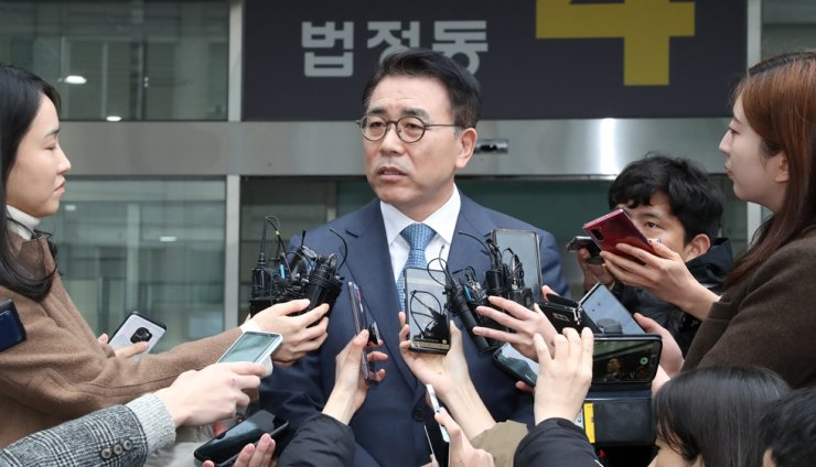 Shinhan Financial Group Chairman Cho Yong-byoung answers questions from reporters at the Seoul Eastern District Court, Wednesday, after being sentenced to a half year in prison suspended for two years for his alleged cronyism. / Yonhap