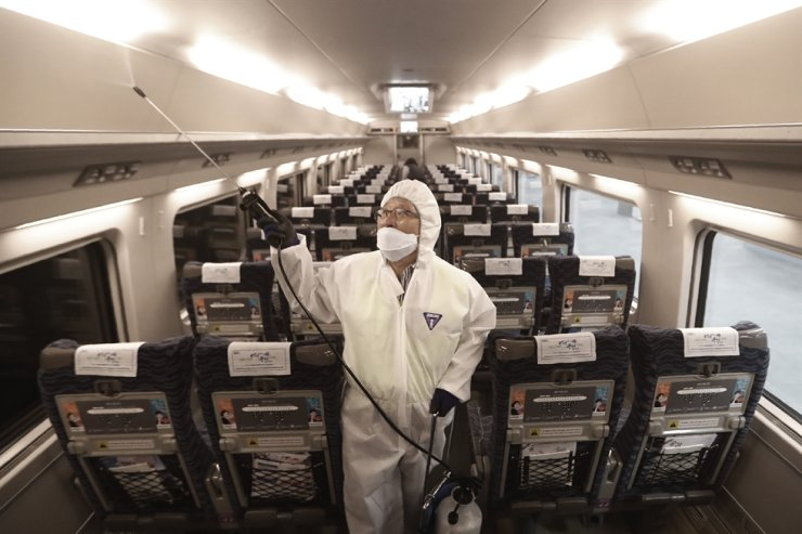An employee sprays disinfectant on a train as a precaution against a new coronavirus at Suseo Station in Seoul, Friday, Jan. 24, 2020. AP