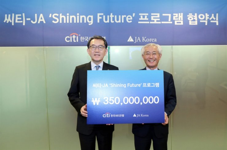 Citibank Korea CEO Park Jin-hei, left, poses with JA Korea CEO Oh Jong-nam at the commercial bank's main branch in Seoul, Wednesday, after donating 350 billion won ($300,000) to the nonprofit organization. They agreed to use the money to help vocational school students find jobs. / Courtesy of Citibank Korea