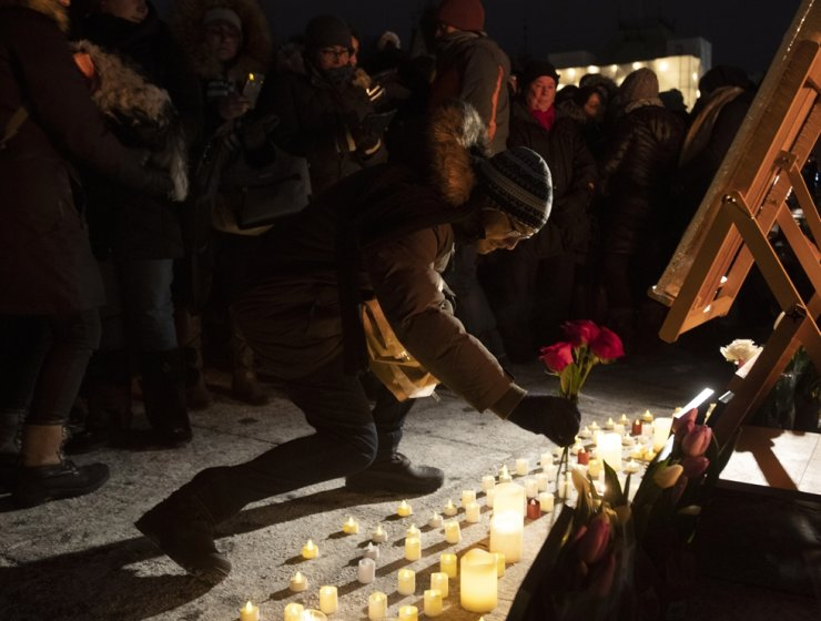 A man places flowers at a candlelight vigil to remember the victims of the Ukraine International Airlines plane crash, Thursday, Jan. 9, 2020, in Ottawa, Ontario. AP